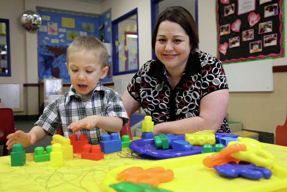 In this April 4, 2012, photo, Kelly Andrus plays with her son Bradley, in his classroom at Children's Choice Learning Centers Inc., in Lewisville, Texas. Bradley, who turns three in a couple of weeks, was diagnosed a year ago with mild autism. For the first time in nearly two decades, experts want to rewrite the definition of autism. Some parents fear that if it's narrowed and their kids lose the label, they may also lose out on special therapist. (AP Photo/Tony Gutierrez) Photo: Tony Gutierrez / AP