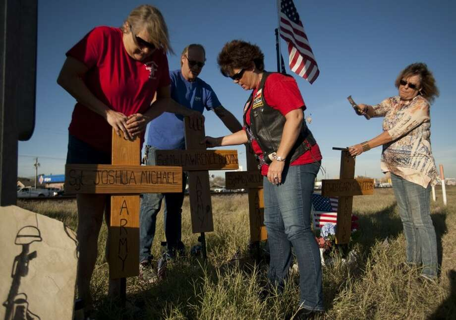 (File Photo) Sandy Dunlap, Ron Masters, Krista Fowler and Georgia Scott, with Patriot Guard Riders and Midland VFW Post 4149 places crosses at the accident site where four veterans died in a train accident hit the trailer in the parade. Tim Fischer\Reporter-Telegram Photo: Tim Fischer