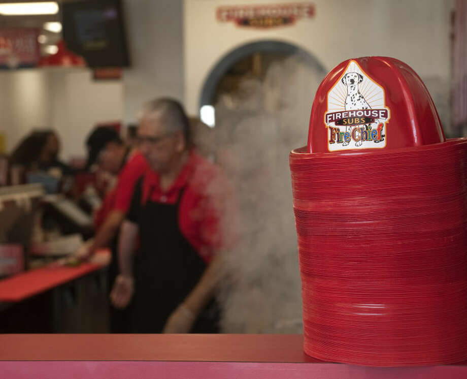 Firehouse Sub hats are ready for kids and adults Monday as sandwiches are prepared for customers at lunch Monday at the new Firehouse Subs restaurant. Tim Fischer\Reporter-Telegram Photo: Tim Fischer