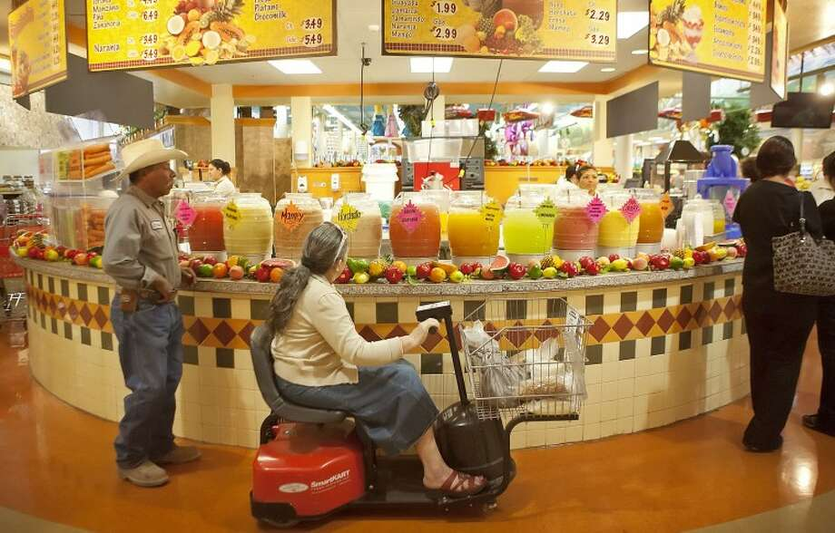Customers look and decide which aguas frescas drink they want to buy Wednesday at the Palapa located inside El Rancho Supermarcado in Odessa. Cindeka Nealy/Reporter-Telegram Photo: Cindeka Nealy