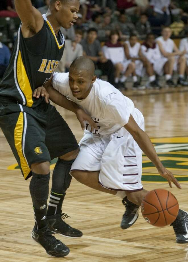 Midland Lee's Anthony McCoy gets called for a push as he tries to dribble around Alief Hastings' Andre Johnson Saturday in the championship game of the Byron Johnston Holiday Classic at the Chaparral Center. Tim Fischer\Reporter-Telegram Photo: Tim Fischer