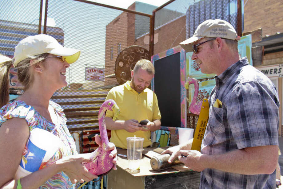 Keith Bynum, center, sells Midlanders Glenda and Emmett Lamon, left and right, a pink metal flamingo Sunday at the Old Sorehead Trade Days in Stanton. Tyler White/Reporter-Telegram Photo: TYLER WHITE