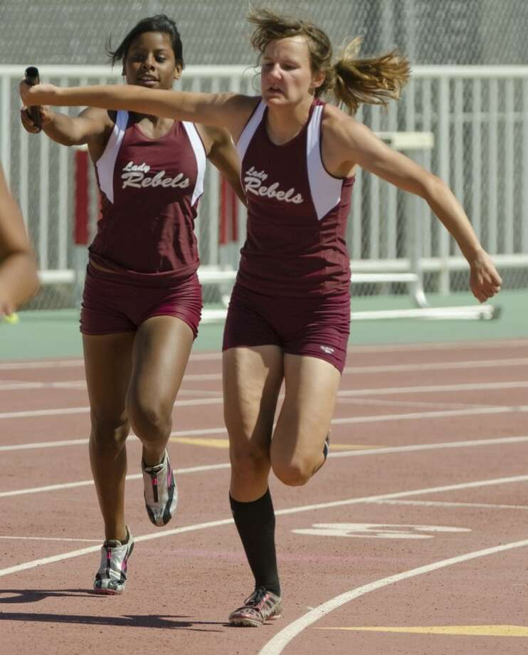 Midland Lee's Latriceia Smith hands off to Tori Rackow in the girls 4x200 meter relay Friday at the 3-AAAAA district meet at Memorial Stadium. Photo by Tim Fischer/Midland Reporter-Telegram Photo: Tim Fischer
