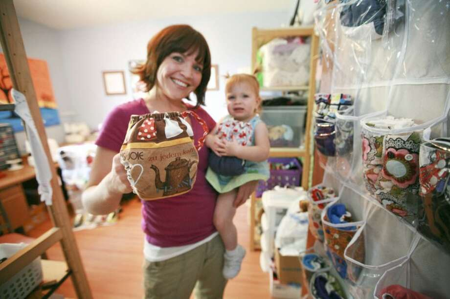 "Sara Scholl and her 17-month-old daughter Sophia show a coffee cup ""Bunzuke Cloth"" that was picked from her collection of diapers she makes in her home and sells online. Scholl also is trying to help set a new world record on Saturday, when she'll try to have many people gathered together and changing diapers at the same time. Cindeka Nealy/Reporter-Telegram Photo: Cindeka Nealy"