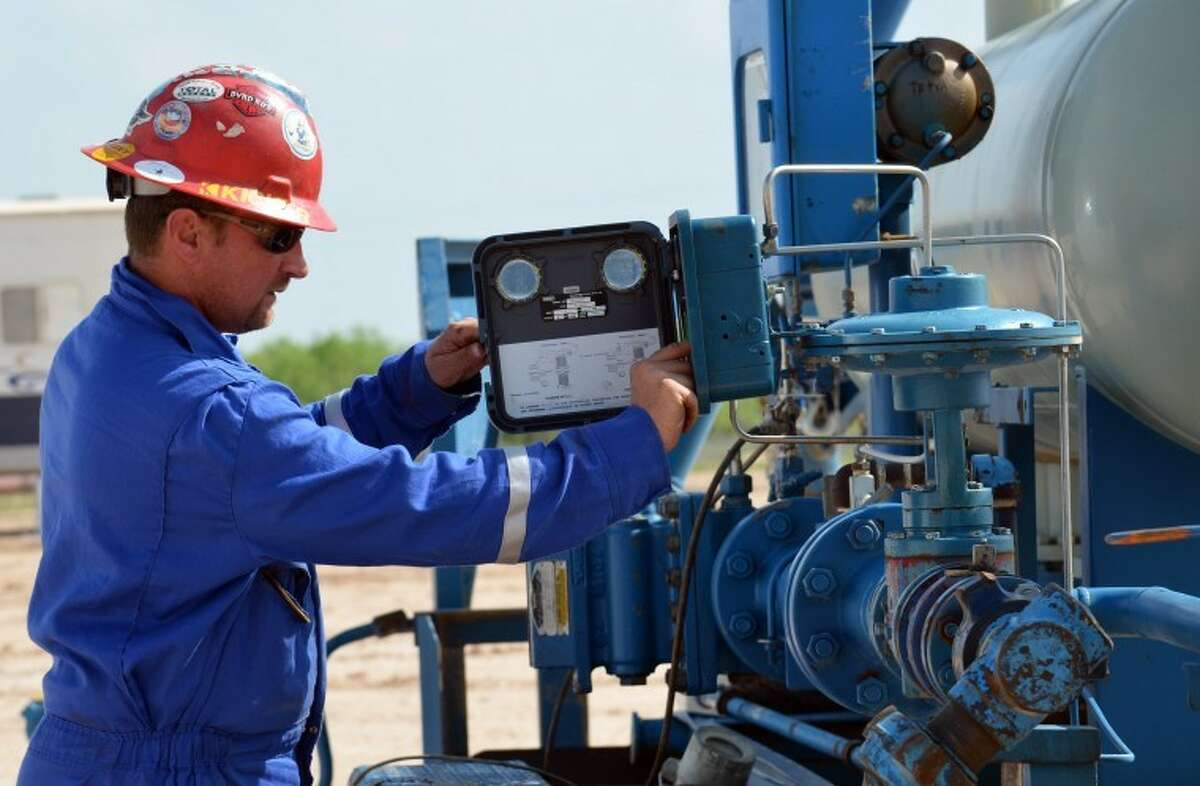 Keith Roberts runs equipment on an oil lot southeast of Garden City in Glasscock County April 12.