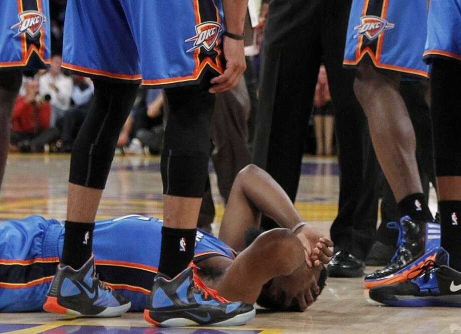 Oklahoma City Thunder players stand over teammate James Harden, lower left, after receiving a flagrant double foul from Los Angeles Lakers' Metta World Peace, who was then ejected, in the first half of an NBA basketball game, Sunday, April 22, 2012, in Los Angeles. (AP Photo/Reed Saxon) Photo: Reed Saxon