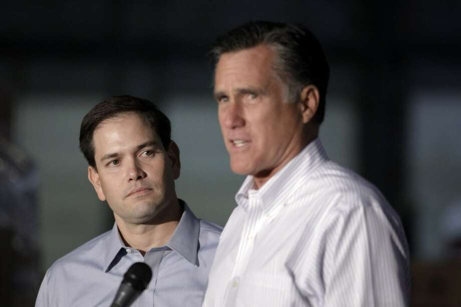 Sen. Marco Rubio, R-Fla. listens at left as Republican presidential candidate, former Massachusetts Gov. Mitt Romney speaks during a news conference prior to a town hall-style meeting in Aston, Pa., Monday, April 23, 2012. (AP Photo/Jae C. Hong) Photo: Jae C. Hong