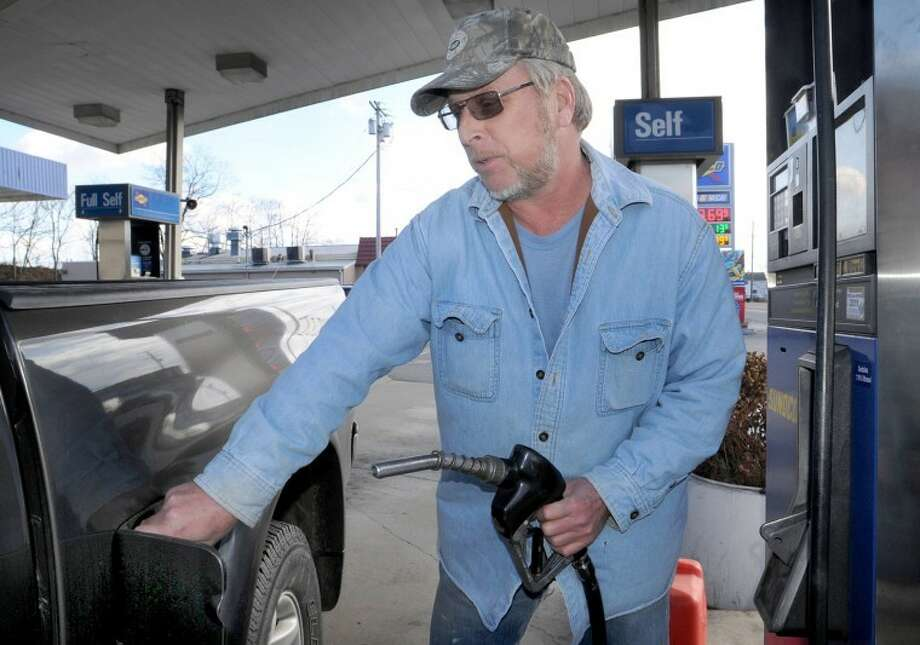 In this Thursday, February 23, 2012, Steve Spencer, who owns Spencer Construction, buys gas for his work truck at Miller's Sunoco, in Chambersburg, Pa. U.S. drivers will pay an average of 24 cents more per gallon for gasoline during this summer's travel season, the government said Tuesday, April 10, 2012. The Energy Information Administration said gasoline should cost an average of $3.95 per gallon from April through September, an increase of 6.3 percent from the same period last year. (AP Photo/Public Opinion, Markell DeLoatch) HAGERSTOWN MD.; WAYNESBORO OUT Photo: Markell DeLoatch