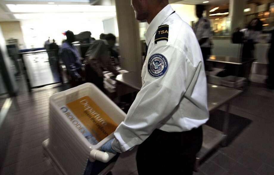 FILE - This Jan. 10, 2007 file photo shows Transportation Security Officer Juan Morales at the Los Angeles International Airport in Los Angeles. Two former and current Transportation Security Administration employees have been arrested and indicted on drug conspiracy charges for allegedly allowing large amounts of cocaine and other drugs to pass through security screening at Los Angeles International Airport last year. Seven people face drug-related charges in a 22-count indictment unsealed Wednesday April 25, 2012, in Los Angeles federal court. (AP Photo/Ann Johansson, File) Photo: Ann Johansson