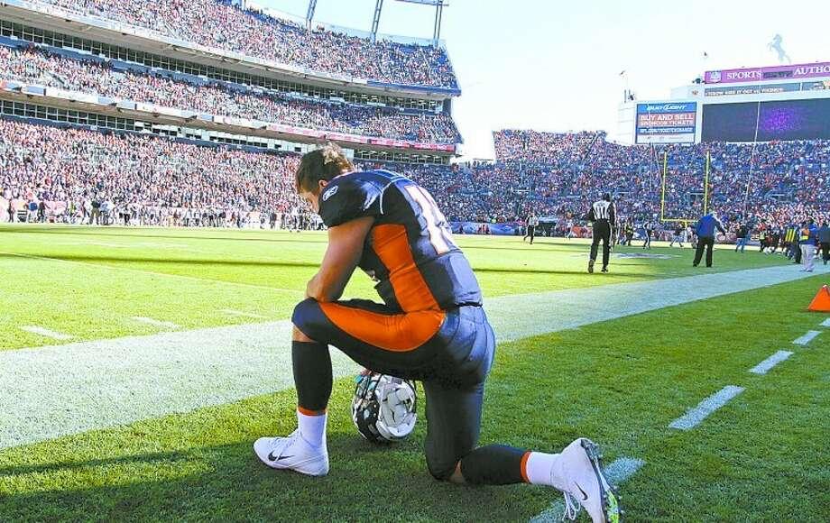 Denver Broncos quarterback Tim Tebow (15) kneels and prays before the start of an NFL football game against the Chicago Bears, Sunday, Dec. 11, 2011, in Denver. (AP Photo/Joe Mahoney) Photo: Joe Mahoney
