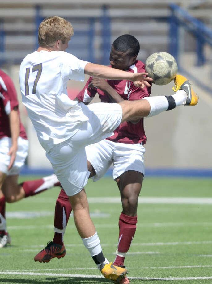 Midland High's William Downing (17) kicks the ball over Lee's Jason McAffee Saturday at Grande Communications Stadium. James Durbin/Reporter-Telegram Photo: JAMES DURBIN