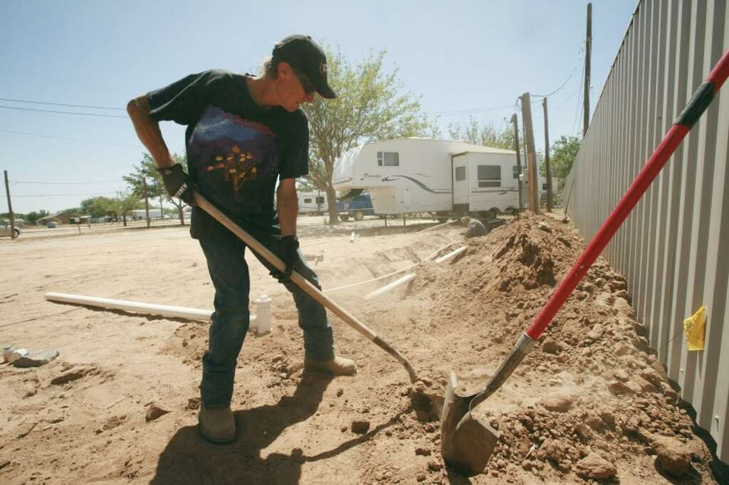Milton Carmack Works On Installing A Drainage And Water Line For New Mobile Home At