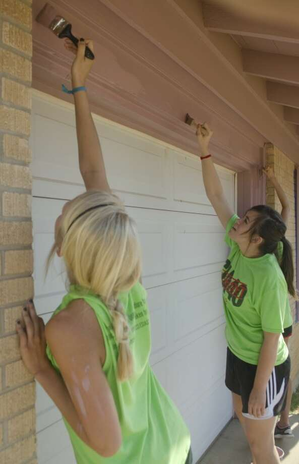 Presley Haner, Destiney Jared and other MCS students paint o home on E. Nobles Wednesday morning as they and other students from Midland Christian worked throughout the city as part of their Day of Service. Photo by Tim Fischer/Midland Reporter-Telegram Photo: Tim Fischer
