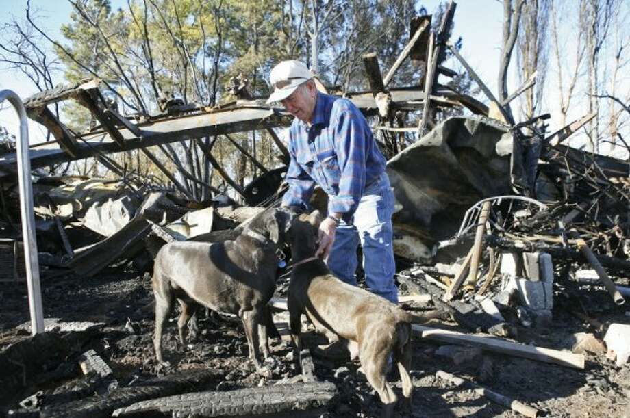 Bobby Gann play's with Missy, from left, Blackie, and Little Bully outside of his trailer that was destroyed by a fire on Saturday. Gann was also able to save two of his other dogs but his three cats, all of his belongings, as well as his Korean War medals were destroyed. Readers of Shanna's column rallied together to help the World War II veteran and his dogs. Cindeka Nealy/Reporter-Telegram