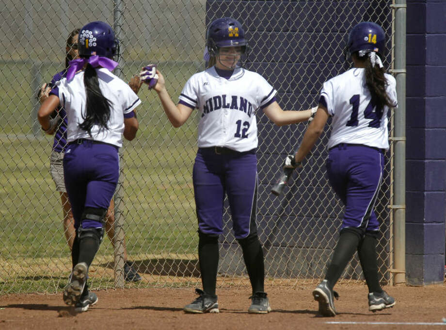 Midland High's Brittany Baggett (center) gives high fives to teammates Lea Lopez (left) and Pini Abila (right) after the two brought in runs against Abilene Cooper on Saturday at Audrey Gill Sports Complex in Midland. James Durbin/Reporter-Telegram Photo: JAMES DURBIN
