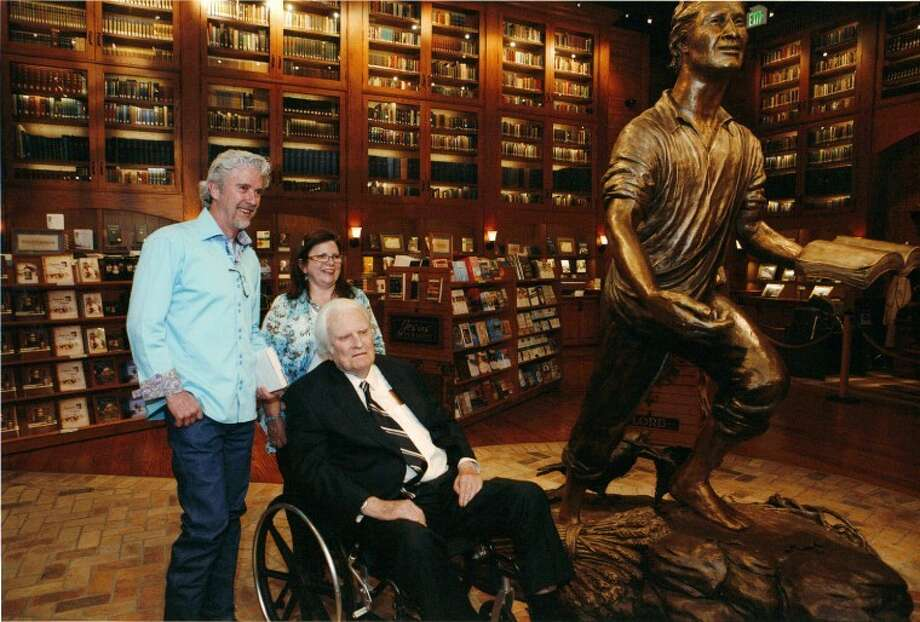 Former Midlanders Tom and Marcey White pose with Billy Graham at the Billy Graham Library in Charlotte, N.C. White was commissioned to create the the 8-foot bronze sculpture. He created a 12-inch replica and donated it for the American Cancer Society's Round-Up auction. Photo: Courtesy Photo