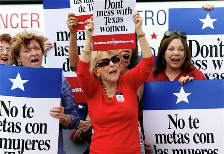 In this March 6, 2012 file photo Mary Green, Peg Armstrong and Jan Perrault hold up signs during Women's Health Express, a bus event held in San Antonio, Texas, to protest the attempt to cut Planned Parenthood out of the state's Women's Health Plan. Federal Judge Lee Yeakel ruled Monday there is sufficient evidence a law barring Planned Parenthood from participating in the Texas' Women's Health Program in unconstitutional and stopped the state from banning the organization from receiving state funds. (AP Photo/San Antonio Express-News, Helen L. Montoya, File) RUMBO DE SAN ANTONIO OUT; NO SALES Photo: Helen L. Montoya / AP2012