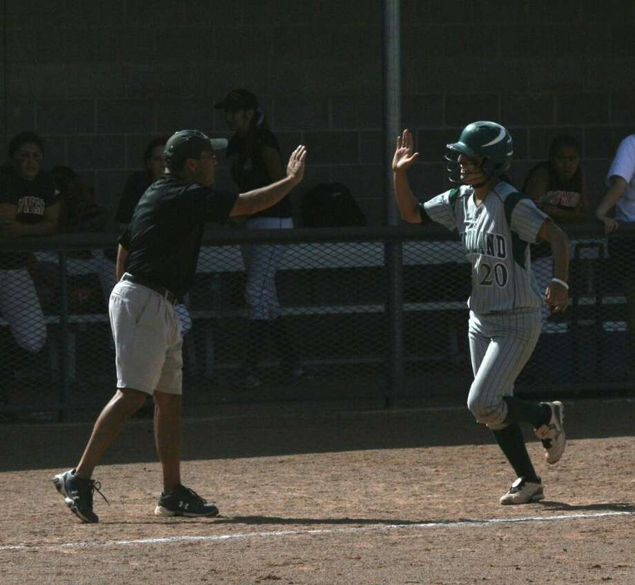 Midland College's Diana De La Paz high fives Lady Chaps coach Tommy Ramos as she rounds third base after hitting a game-winning home run against Howard College on Friday in Lubbock. Forrest Allen/MC Athletics