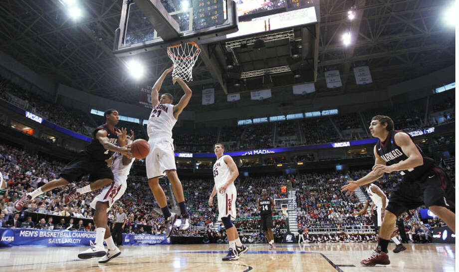 Harvard's Siyani Chambers, left, passes to his teammate Jonah Travis, right, as Arizona's Jordin Mayes, second from left, Brandon Ashley (21) and Kaleb Tarczewski (35) defend during the first half in a third-round game in the NCAA men's college basketball tournament in Salt Lake City on Saturday, March 23, 2013. (AP Photo/George Frey) Photo: George Frey