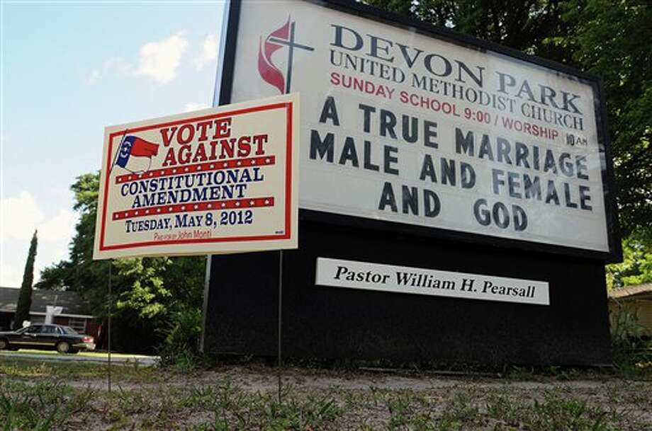 Signs display messages about gay marriage in front of the Devon Park United Methodist Church polling site on Tuesday, May 8, 2012, in Wilmington, N.C. North Carolina could be the next state to pass a constitutional amendment defining marriage as solely between a man and a woman. Voters are casting their ballots Tuesday. (AP Photo/The Star-News, Ken Blevins) Photo: Ken Blevins / AP2012