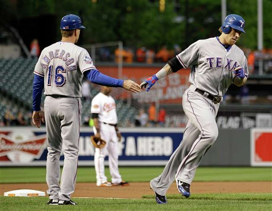 Texas Rangers' Josh Hamilton, right, high-fives third base coach Dave Anderson as he rounds the bases after hitting a two-run home run in the first inning of a baseball game against the Baltimore Orioles in Baltimore, Tuesday, May 8, 2012. (AP Photo/Patrick Semansky) Photo: Patrick Semansky / AP