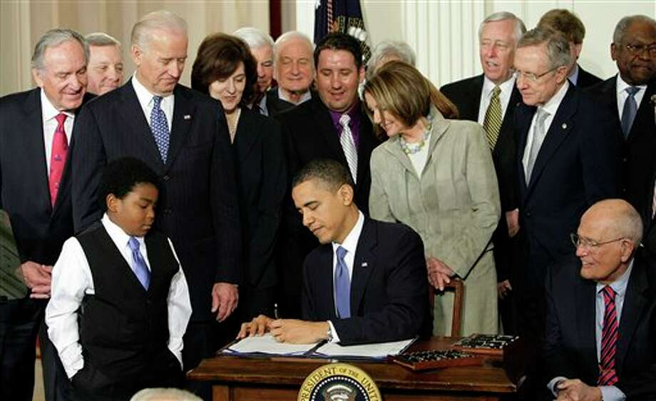 FILE - In this March 23, 2010 file photo, Marcelas Owens of Seattle, left, Rep. John Dingell, D-Mich., right, and others, look on as President Barack Obama signs the health care bill in the East Room of the White House in Washington. Medical claims costs _ the biggest driver of health insurance premiums _ will jump an average 32 percent for individual policies under President Barack Obama's overhaul, according to a study by the nation's leading group of financial risk analysts. Recently released to its members, the report from the Society of Actuaries could turn into a big headache for the Obama administration at a time when many parts of the country remain skeptical about the Affordable Care Act. (AP Photo/J. Scott Applewhite, File) Photo: J. Scott Applewhite / AP
