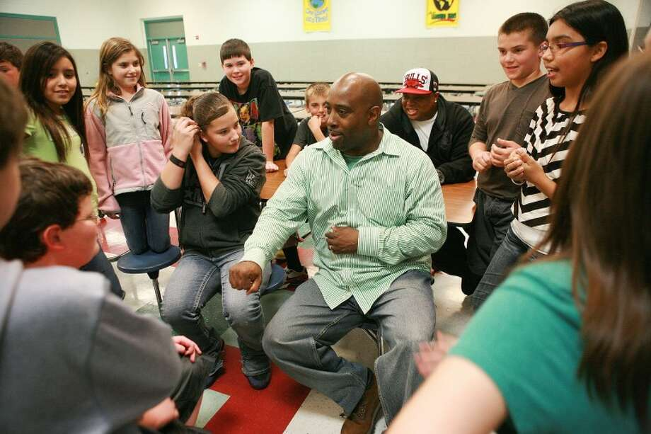 Melvin Adams, a former Harlem Globetrotter, entertains and listens to a group of sixth-graders after his inspirational comedy show Monday at Emerson Elementary. Adams used comedy, basketball and music to let the children know that they have value and sky's the limit in what they can achieve. Cindeka Nealy/Reporter-Telegram Photo: Cindeka Nealy