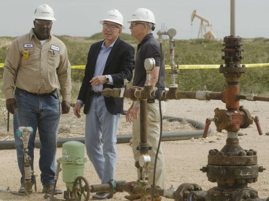 Interior Secretary Ken Salazar, center, looks over a working well site Wednesday as Rock Lee, MSU lease operator with ConocoPhillips, left and Ty Maxey, Permian Operations Manager answer questions about the operation during a tour of a well field in Andrews County. Photo by Tim Fischer/Midland Reporter-Telegram Photo: Tim Fischer