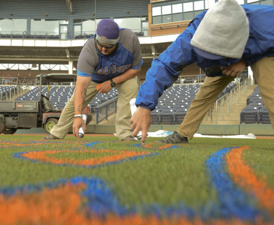 Head greenskeeper Eric Campbel left, and ssistant greenskeeper Patrick Barnaby, paint the logo behind homeplate Wednesday moring as they work on painting the logos on the field at CitiBank Ballpark in preparation of the home opener Thursday against NW Arkansas. Tim Fischer\Reporter-Telegram Photo: Tim Fischer