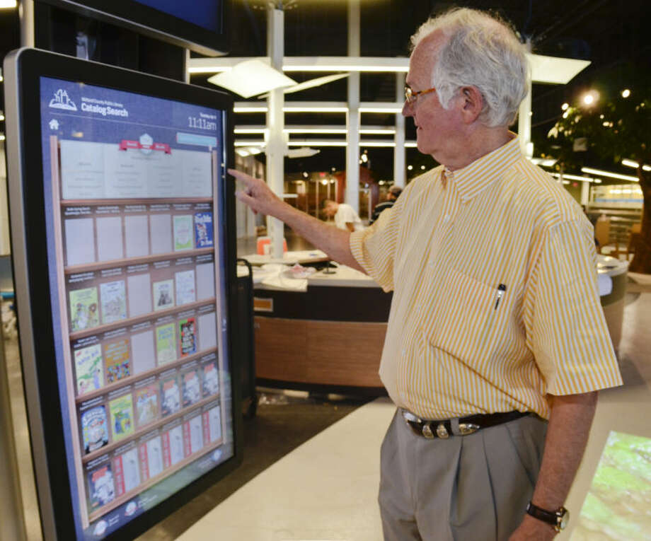 Midland County Judge Mike Bradford demonstrates one of the touchscreen displays, found throughout the library, used to help locate books, magazines, or music. Tim Fischer\Reporter-Telegram Photo: Tim Fischer