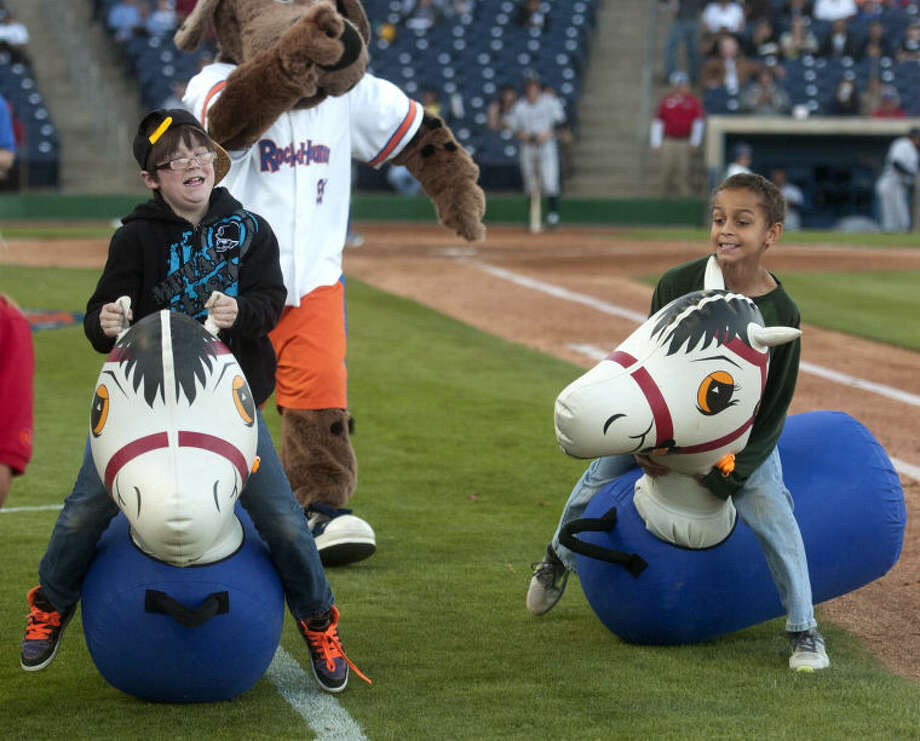 RockHounds fans from left, Taylur Patterson, age 10, and Evan Hill, age 11, compete in the 'Pony Hop' game between innings during the home opener against North Arkansas Thursday at Citibank Ballpark. James Durbin/Reporter-Telegram Photo: JAMES DURBIN