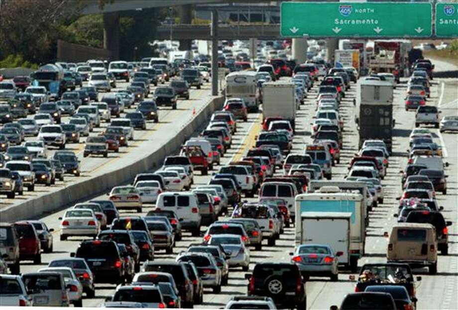 In this May 28, 2010 file photo, the rush hour commute starts in early afternoon and with greater intensity as traffic is jammed in both directions on Interstate 405 on the Westside of Los Angeles as commuters and vacationers hit the road. Cheaper gas won't be enough to spur many more road trips this summer. Americans are too worried about their jobs and the economy to feel relief. Economists and tourism experts are expecting only a small uptick in summer travelers. Gas prices are lower, but still high enough to keep lower-income Americans off the road. The job market is improving, but still shaky. And household debt remains high. The bulk of road trippers, experts say, are taking shorter trips, reducing food and entertainment expenses or staying closer to home to conserve cash. (AP Photo/Reed Saxon, file) Photo: Reed Saxon / AP2010