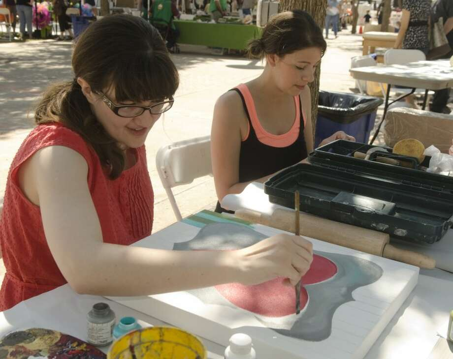 Molly Swanson works on a painting as Danielle Kiser works on a clay piece Saturday at their booth, the Flying Olive, at Celebration of the Arts. The women are among a group of young artists who find inspiration in Midland. Photo: Tim Fischer/Reporter-Telegram