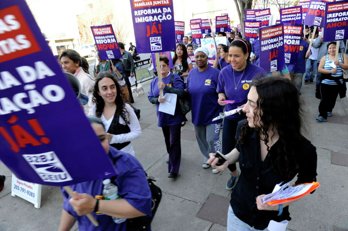 Camila, left, and Carolina Bortolleto, march down Main Street in Danbury, Conn., during an immigration reform rally, Tuesday, April 9, 2013.