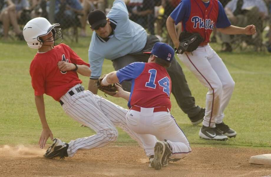 Phillies' #14, Smith Essman puts the tag on Braves' #88 Adam Becker as he tries for a triple Wednesday evening in the National League final of the Little League City Tournament. Photo by Tim Fischer/Midland Reporter-Telegram Photo: Tim Fischer