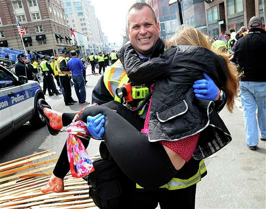 In this Monday, April 15, 2013 photo, Boston Firefighter James Plourde carries an injured girl away from the scene after a bombing near the finish line of the Boston Marathon in Boston. The FBI's investigation into the bombings at the Boston Marathon was in full swing Tuesday, with authorities serving a warrant on a suburban Boston home and appealing for any private video, audio and still images of the blasts that killed at least three and wounded more than 170. (AP Photo/MetroWest Daily News, Ken McGagh) MANDATORY CREDIT Photo: Ken McGagh / METROWEST DAILY NEWS2013
