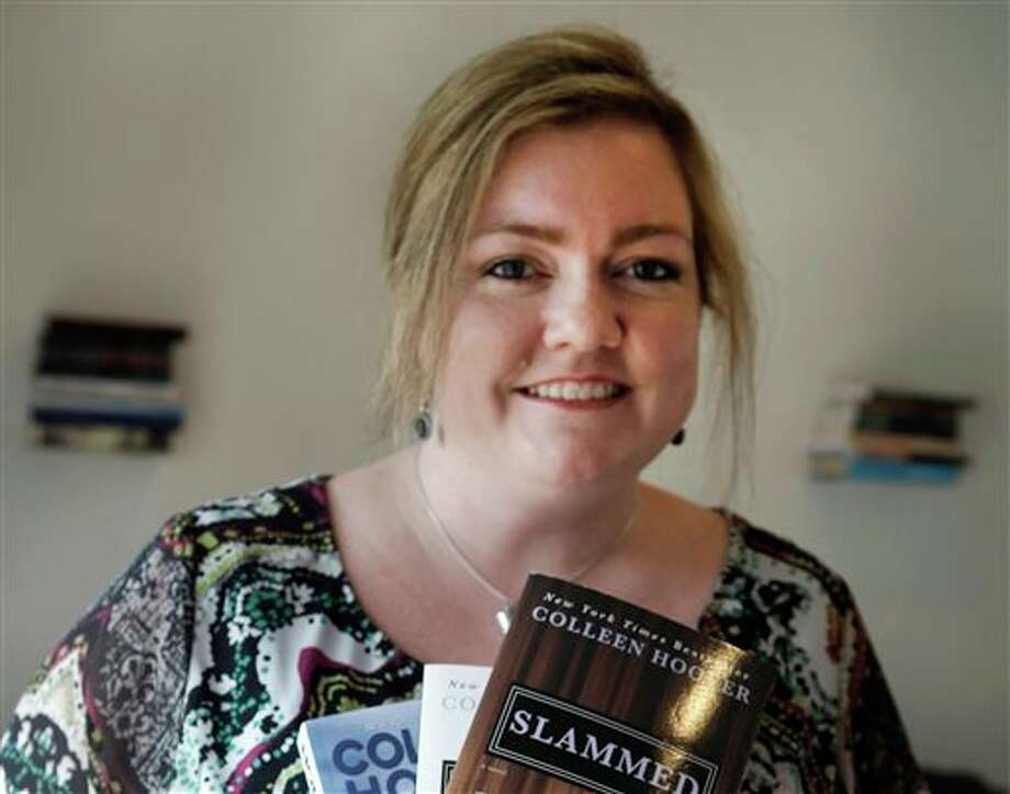 In the photo made Tuesday, Feb. 5, 2013, self publishing author Colleen Hoover posses and holds copies her books in Sulphur Springs, Texas. Hoover's romance novels books have made the New York Times bestseller list. (AP Photo/LM Otero) Photo: LM Otero / AP