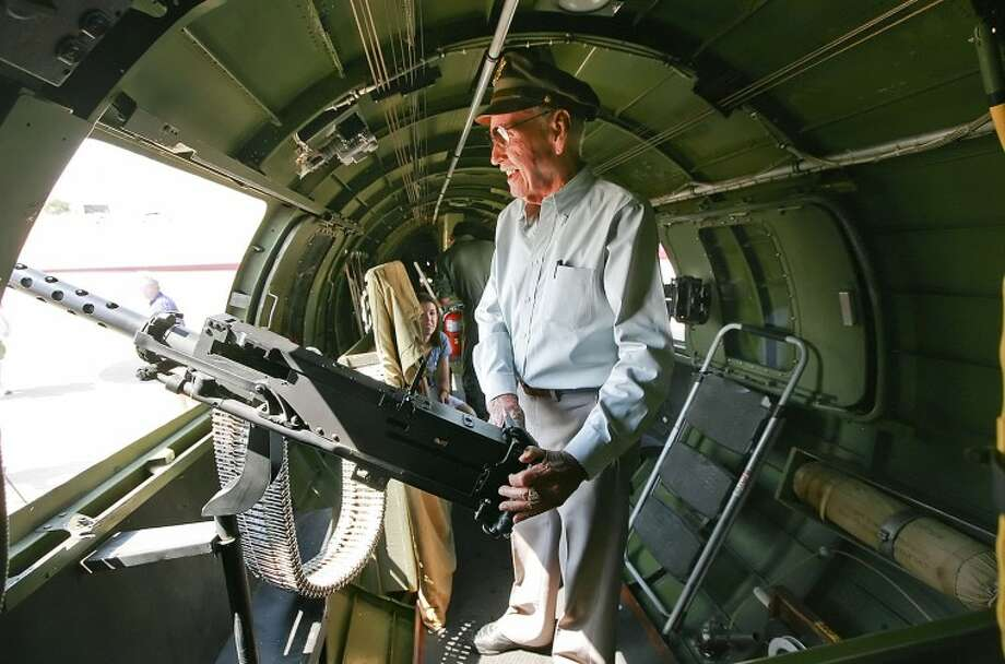 B-17G Flying Fortress Engineer and Top Turret Gunner John Campbell grabs a hold of a machine gun, located inside the fuselage of the bomber, Saturday at Midland International Airport. Campbell flew 35 missions in a bomber similar to this one with the 92nd Bomb Group during World War II. Cindeka Nealy/Reporter-Telegram Photo: Cindeka Nealy