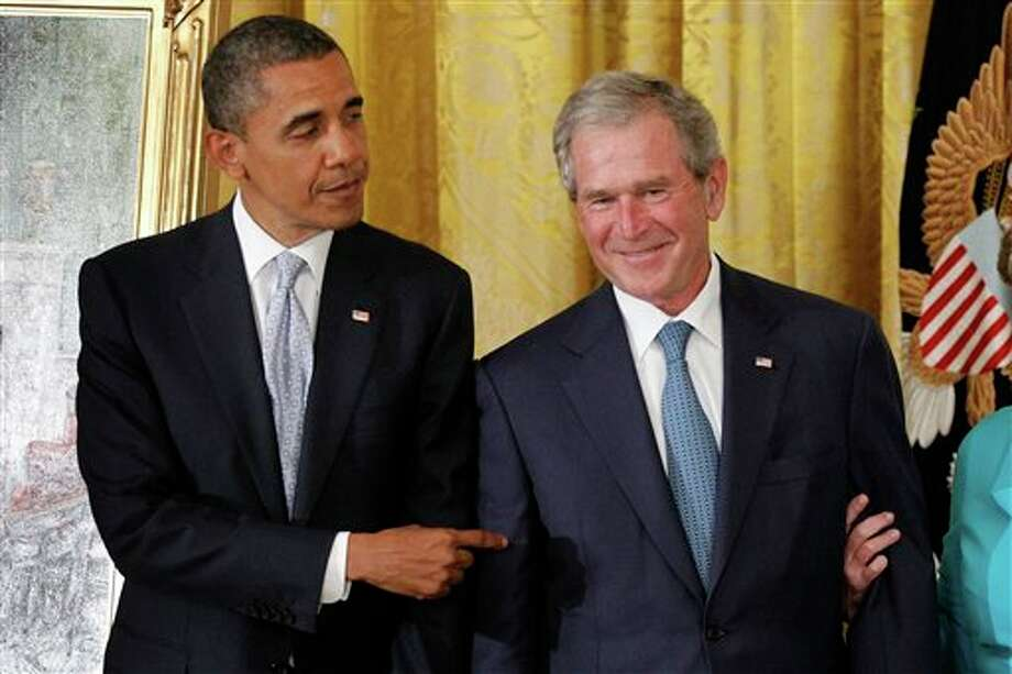 President Barack Obama points to former President George W. Bush during a ceremony to unveil his official portrait, Thursday, May 31, 2012, in the East Room at the White House in Washington. (AP Photo/Charles Dharapak) Photo: Charles Dharapak / AP2012
