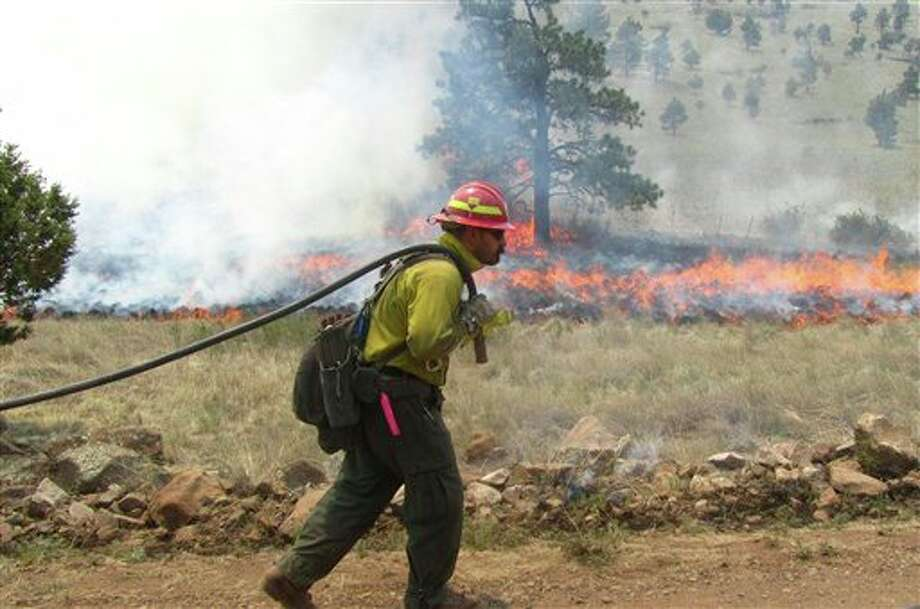 A firefighter works an area along the northwest perimeter of a massive blaze in the Gila National Forest in New Mexico in this photo made on Wednesday, May 30, 2012, and released by the U.S. Forest Service Friday. More than 1,200 firefighters are battling the fire that has burned nearly 217,000 acres in an isolated mountainous area of southwestern New Mexico. (AP Photo/U.S. Forest Service, Alan Sinclair) Photo: Alan Sinclair / U.S. Forest Service