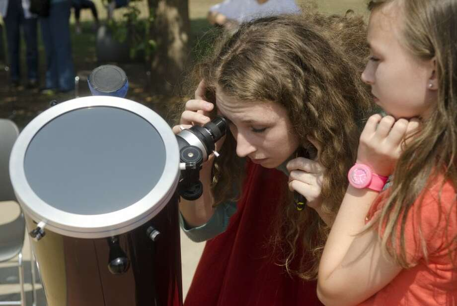 Katie Hornell looks at the sun through a specially equiped telescope as her sister, Madelyn waits Tuesday evening outside the Blakemore Planetarium as they and others came out to watch the planet Venus pass between the sun and Earth. Photo by Tim Fischer/Midland Reporter-Telegram Photo: Tim Fischer