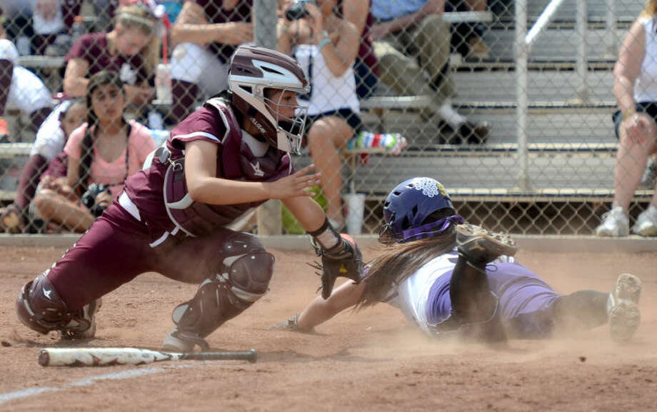 Lee's Destiny Reyes tries to tag Midland High's Lexi Lopez out at home Saturday at Audrey Gill Sports Complex. James Durbin/Reporter-Telegram Photo: JAMES DURBIN