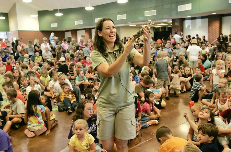 Abilene Zoo Education Curator Joy Harsh shows a crowd of more than 300-children and their parents an American alligator Wednesday during the Midland County Public Library's, Summer Reading Program kick-off at the Horseshoe. Cindeka Nealy/Reporter-Telegram Photo: Cindeka Nealy