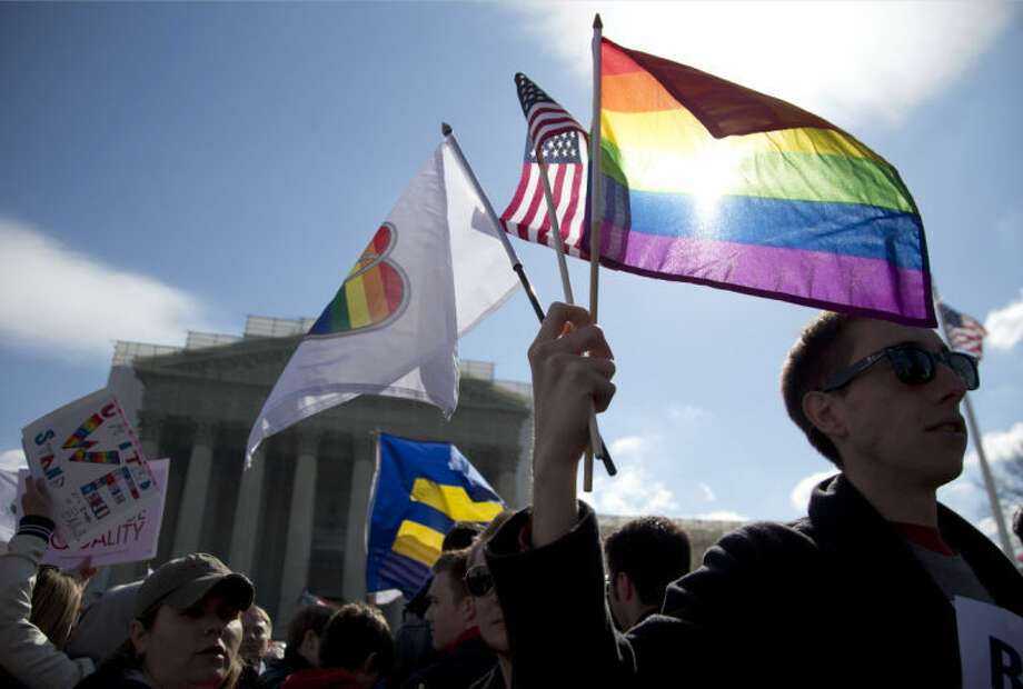 Kevin Coyne of Washington holds flags in front of the Supreme Court in Washington, Wednesday, March 27, 2013. The U.S. Supreme Court, in the second day of gay marriage cases, turned Wednesday to a constitutional challenge to the federal law that prevents legally married gay Americans from collecting federal benefits generally available to straight married couples. (AP Photo/Carolyn Kaster) Photo: Carolyn Kaster