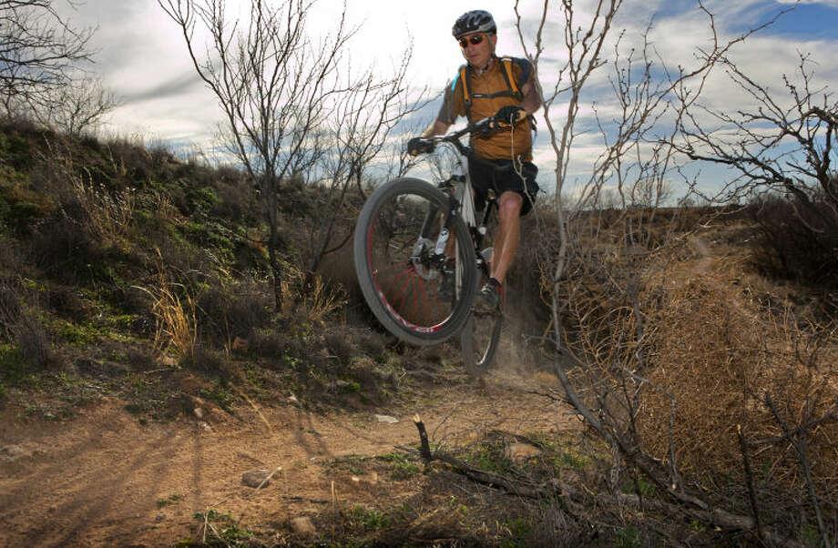 Steve Mitchell (gold shirt), Permian Basin Bicycle Association mountain bike director, rides a trail at the mountain bike park in Odessa Saturday. James Durbin/Reporter-Telegram Photo: JAMES DURBIN
