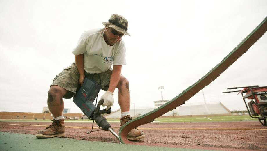 Rob Dean uses a jackhammer to trim away the portion of track that is being replaced Friday at Memorial Stadium. Cindeka Nealy/Reporter-Telegram Photo: Cindeka Nealy