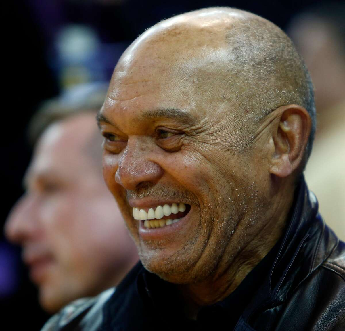 Baseball Hall of Famer Reggie Jackson laughs as he watches Golden State Warriors' Stephen Curry drain a deep 3-pointer during pregame of Warriors' game against Charlotte Hornets at Oracle Arena in Oakland, Calif., on Monday, January 4, 2016.
