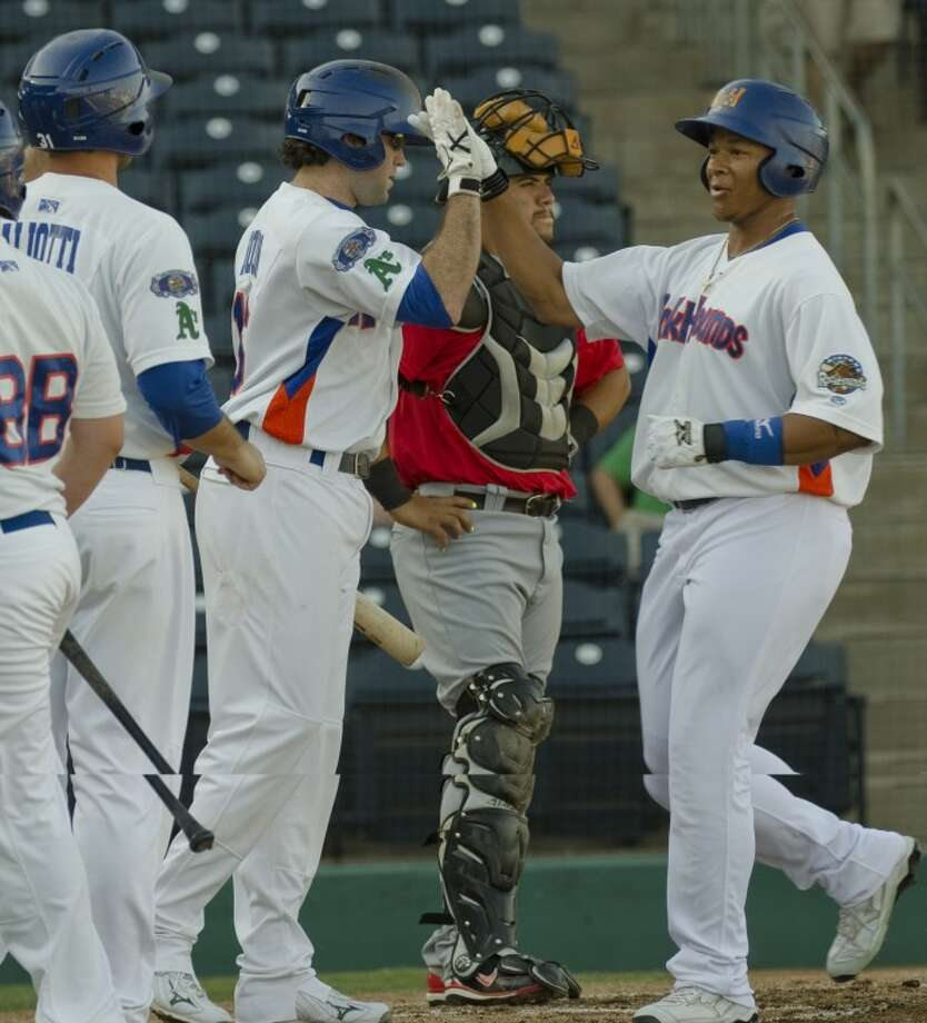 RockHounds' Michael Choice, right, gets a high five from Josh Horton and Anthony Aliotti as he crosses home plate on a three run homerun Monday evening at CitiBank Ballpark. Photo by Tim Fischer/Midland Reporter-Telegram Photo: Tim Fischer