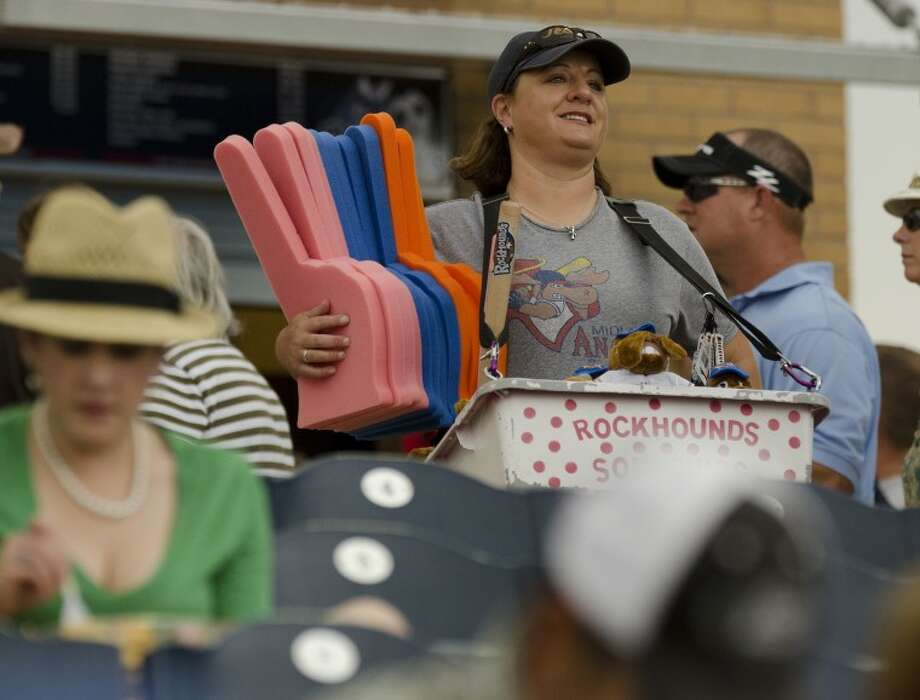 Kristi Shirley, a physical education teacher at Washington Math and Science Institute, sells RockHounds souvenirs at home games as a way to make extra money, and be able to watch her favorite sport.  Photo: Tim Fischer/Reporter-Telegram