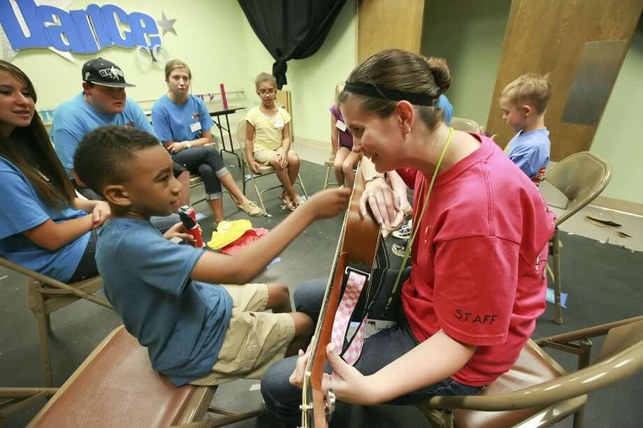 """Nicholas Crowder, 7, strums a guitar as Cara McBurney plays """"Good By"""" Tuesday as the group concludes their music session during the We Are the World Camp at the Midland Children's Rehabilitation Center. Photo: Cindeka Nealy/Reporter-Telegram"""